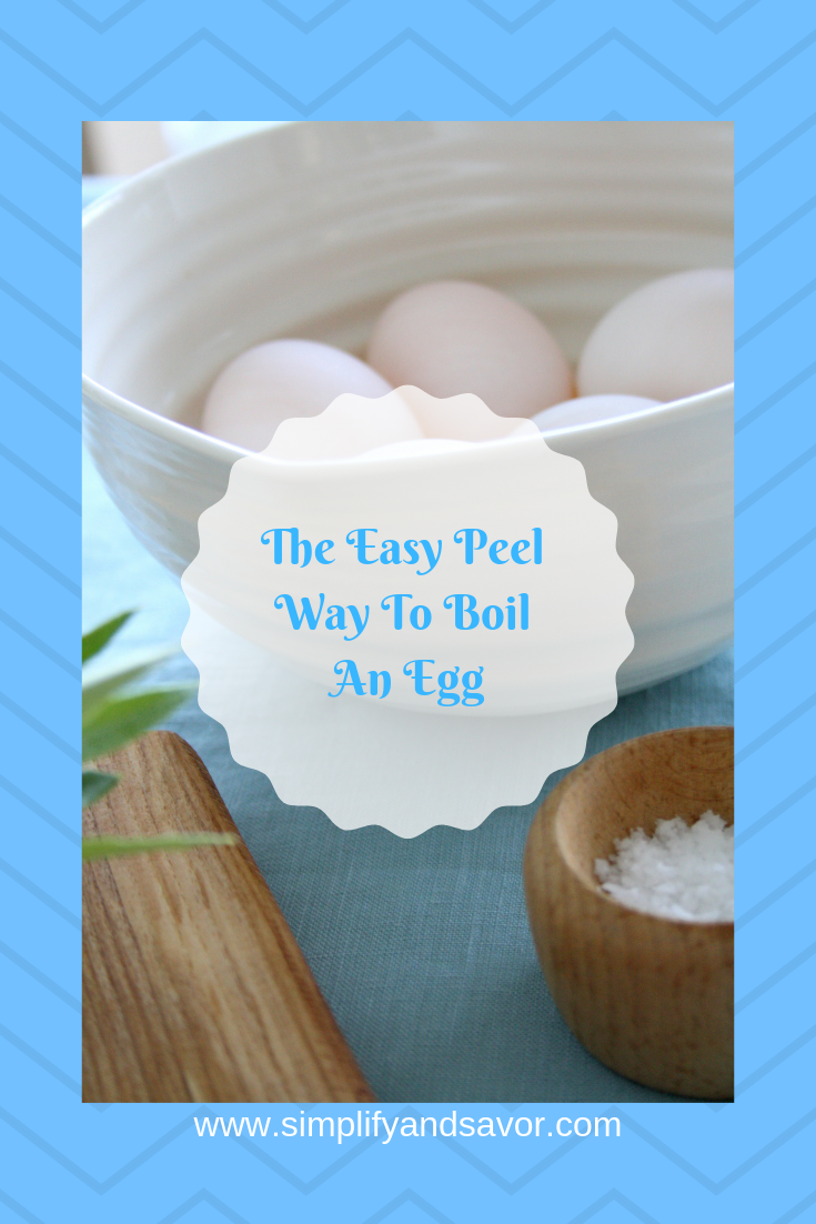 A bowl of eggs and a wooden bowl and cutting board, with the text The Easy Peel Way to Boil an Egg