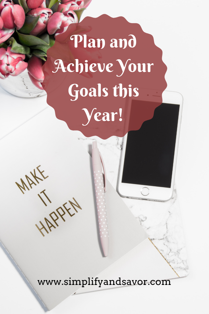 A folder with the words make it happen sitting on a desk with a pen on top of it and an iphone sitting next to it. Then my text stating Achieve your goals this year.